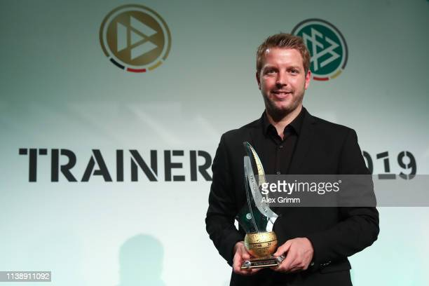 Head coach of Werder Bremen Florian Kohfeldt poses with the trophy after being awarded as the head coach of the year 2018 during the Coaching Award...