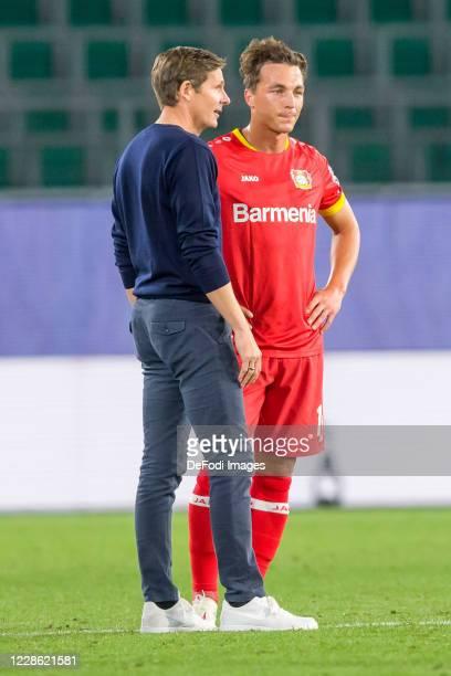 head coach Oliver Glasner of VfL Wolfsburg and Julian Baumgartlinger of Bayer 04 Leverkusen speaks with during the Bundesliga match between VfL...