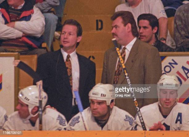 Head coach Pat Burns and assistant coach Mike Kitchen of the Toronto Maple Leafs watch the play against the Detroit Red Wings during NHL game action...
