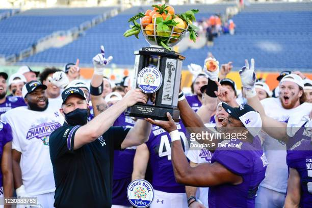Head coach Pat Fitzgerald and Jesse Brown of the Northwestern Wildcats raise the trophy after defeating the Auburn Tigers to win the Vrbo Citrus Bowl...