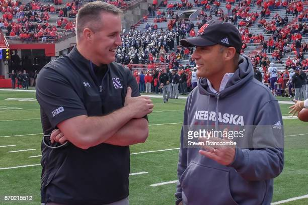 Head coach Pat Fitzgerald of the Northwestern Wildcats and head coach Mike Riley of the Nebraska Cornhuskers meet before the contest at Memorial...