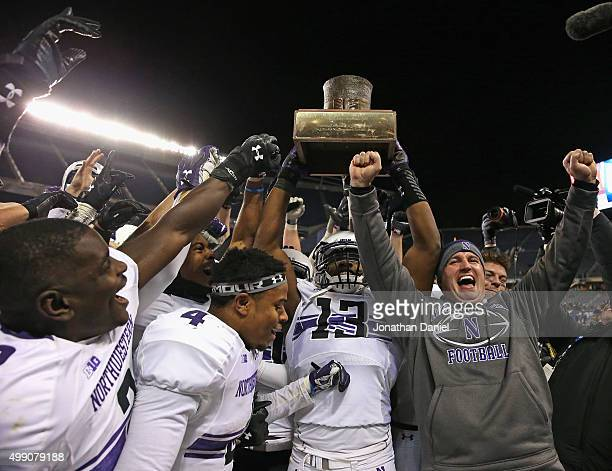 Head coach Pat Fitzgerald of the Northwestern Wildcats celebrates with his team including Traveon Henry, Solomon Vault and Deonte Gibson as they hold...