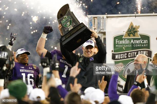 Head coach Pat Fitzgerald of the Northwestern Wildcats raises the trophy after defeating the Kentucky Wildcats 2423 to win the Music City Bowl at...