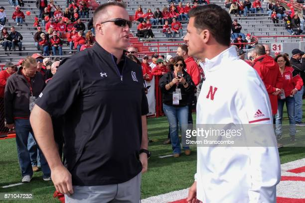 Head coach Pat Fitzgerald of the Northwestern Wildcats talks with defensive coordinator Bob Diaco of the Nebraska Cornhuskers before the game at...