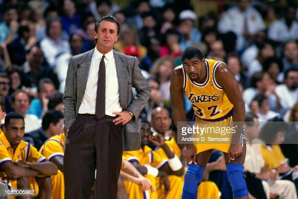 Head Coach Pat Riley and Magic Johnson of the Los Angeles Lakers look on during a game circa 1989 at The Forum in Inglewood, California. NOTE TO...