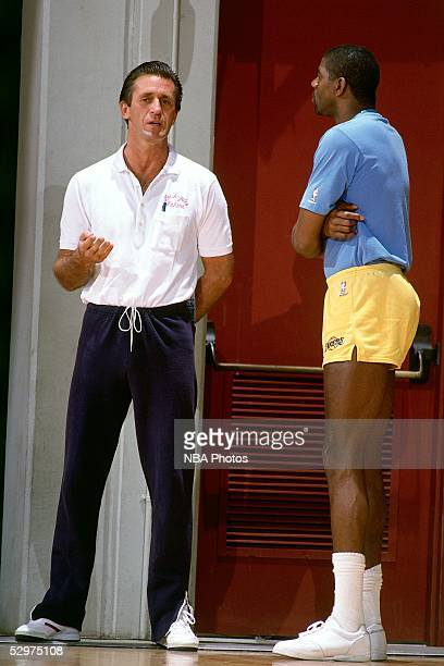 Head Coach Pat Riley of the Los Angeles Lakers talks with 'Magic' Johnson during a Lakers practice session circa 1988 in Los Angeles California NOTE...