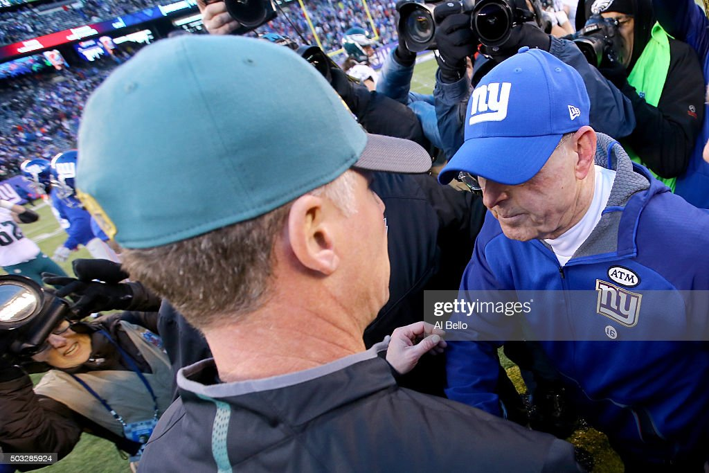 Head coach Pat Shurmur of the Philadelphia Eagles shakes hands with head coach Tom Coughlin of the New York Giants after their game at MetLife Stadium on January 3, 2016 in East Rutherford, New Jersey. The Eagles defeated the Giants with a score of 35 to 30.