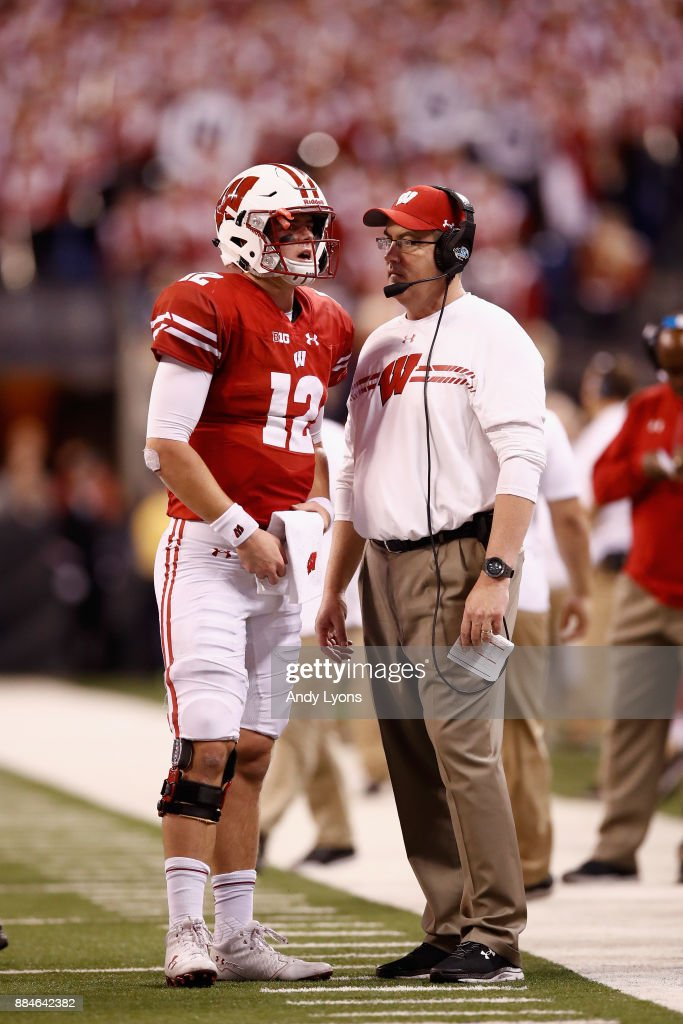 Head coach Paul Chryst of the Wisconsin Badgers talks with quarterback Alex Hornibrook #12 as they take on the Ohio State Buckeyes during the Big Ten Championship game at Lucas Oil Stadium on December 2, 2017 in Indianapolis, Indiana. The Ohio State Buckeyes won 27-21.
