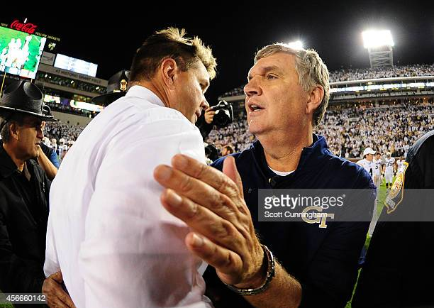 Head Coach Paul Johnson of the Georgia Tech Yellow Jackets is congratulated after the game by Head Coach Al Golden of the Miami Hurricanes at Bobby...
