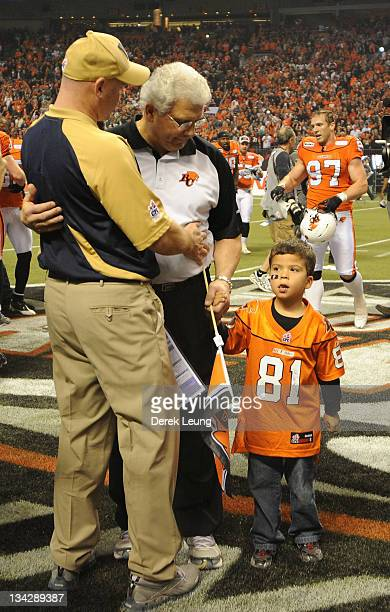 Head coach Paul LaPolice of the Winnipeg Blue Bombers congratulates head coach Wally Buono of the BC Lions in front of Wally's grandson during the...