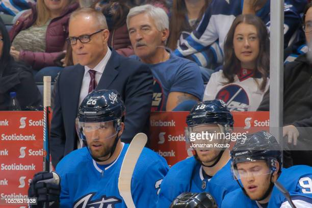 Head Coach Paul Maurice Blake Wheeler Bryan Little and Andrew Copp of the Winnipeg Jets look on from the bench during first period action against the...