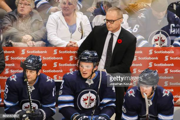 Head Coach Paul Maurice Matt Hendricks Brendan Lemieux and Andrew Copp of the Winnipeg Jets look on from the bench during second period action...