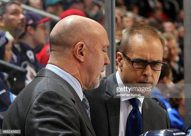 Head Coach Paul Maurice of the Winnipeg Jets discusses strategy with Assistant Coach Charlie Huddy during a second period stoppage in play against...