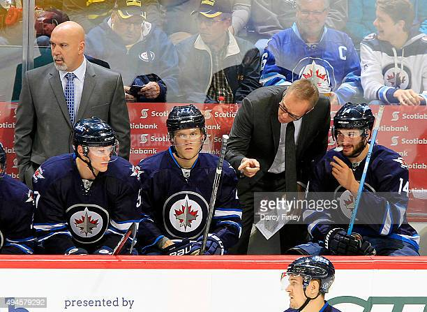 Head Coach Paul Maurice of the Winnipeg Jets instructs Tyler Myers Nikolaj Ehlers and Anthony Peluso on the bench during second period action against...