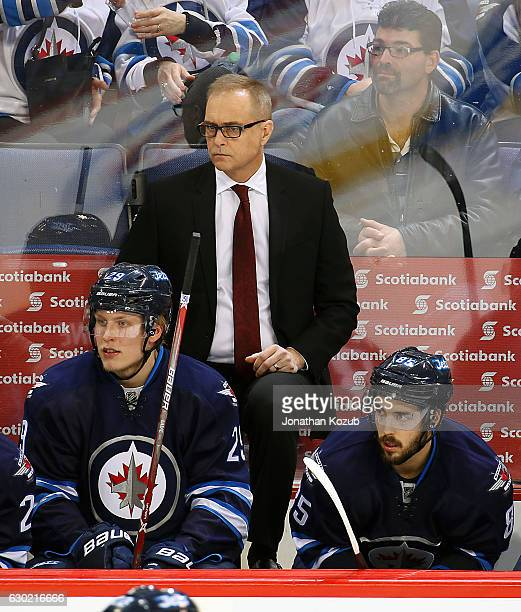 Head Coach Paul Maurice Patrik Laine and Mathieu Perreault of the Winnipeg Jets look on from the bench during third period action at the MTS Centre...