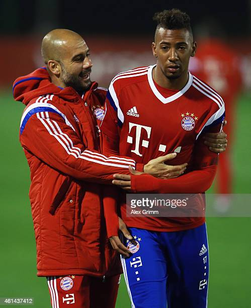 Head coach Pep Guardiola hugs Jerome Boateng during day 4 of the Bayern Muenchen training camp at ASPIRE Academy for Sports Excellence on January 12...