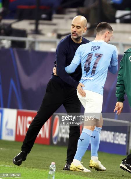 Head coach Pep Guardiola of Manchester City and Foden of Manchester City gestures during the UEFA Champions League Round of 16 match between Borussia...