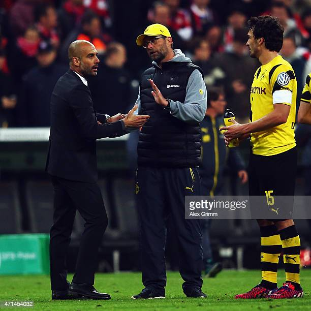 Head coach Pep Guardiola of Muenchen discusses with head coach Juergen Klopp and Mats Hummels of Dortmund during the DFB Cup Semi Final match between...