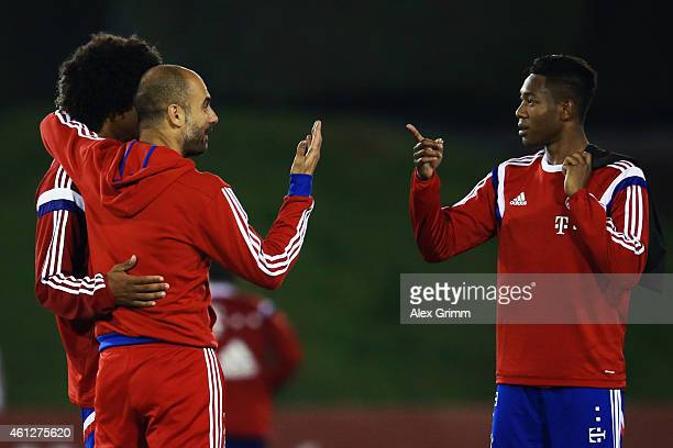 Head coach Pep Guardiola talks to Dante and David Alaba during day 2 of the Bayern Muenchen training camp at ASPIRE Academy for Sports Excellence on...