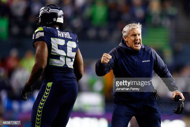 Head coach Pete Carroll and defensive end Cliff Avril of the Seattle Seahawks celebrate in the fourth quarter while taking on the San Francisco 49ers...