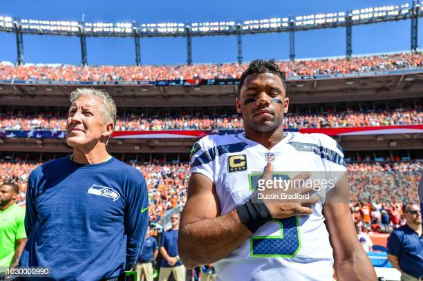 Head coach Pete Carroll and quarterback Russell Wilson of the Seattle Seahawks stand during the national anthem before a game against the Denver...