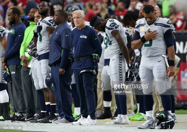 Head coach Pete Carroll Jarod Brown and Russell Wilson of the Seattle Seahawks stand with the team for the National Anthem during an NFL game against...