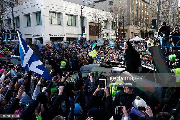 Head coach Pete Carroll of Seattle Seahawks waves to fans during a parade to celebrate their victory in Super Bowl XLVII on February 5 2014 in...