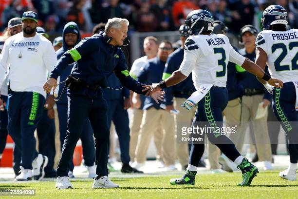 Head Coach Pete Carroll of the Seattle Seahawks congratulates Russell Wilson after scoring a touchdown during the first quarter of the game against...