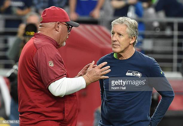 Head coach Pete Carroll of the Seattle Seahawks listens to head coach Bruce Arians of the Arizona Cardinals talk prior to the NFL game at University...