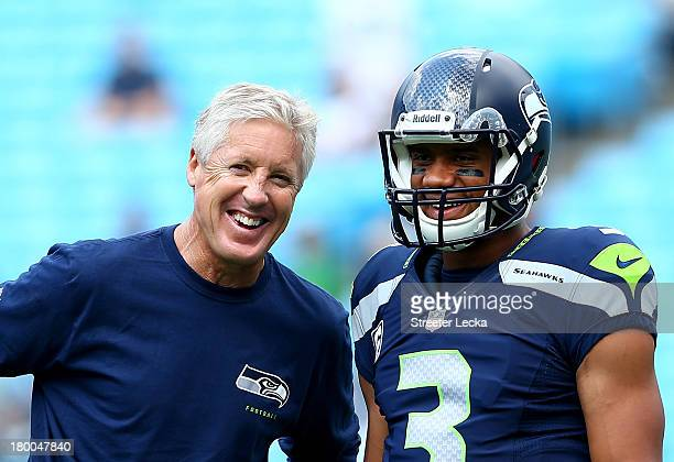 Head coach Pete Carroll of the Seattle Seahawks talks with his quarterback Russell Wilson of the Seattle Seahawks before their game against the...