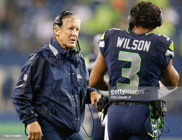 Head coach Pete Carroll of the Seattle Seahawks talks with quarterback Russell Wilson during the preseason game against the Oakland Raiders at...