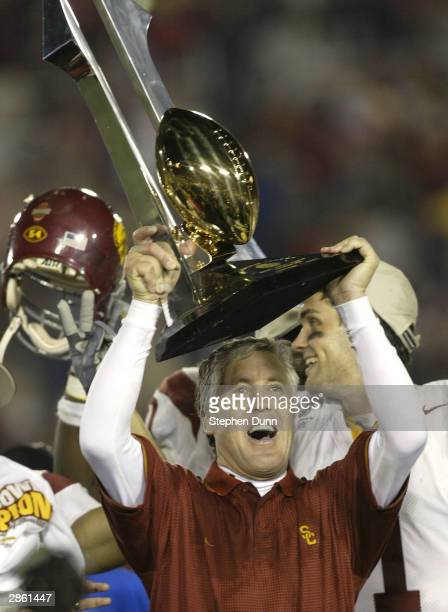 Head coach Pete Carroll of the USC Trojans celebrates with the Tournament of Roses trophy after defeating the Michigan Wolverines in the 2004 Rose...