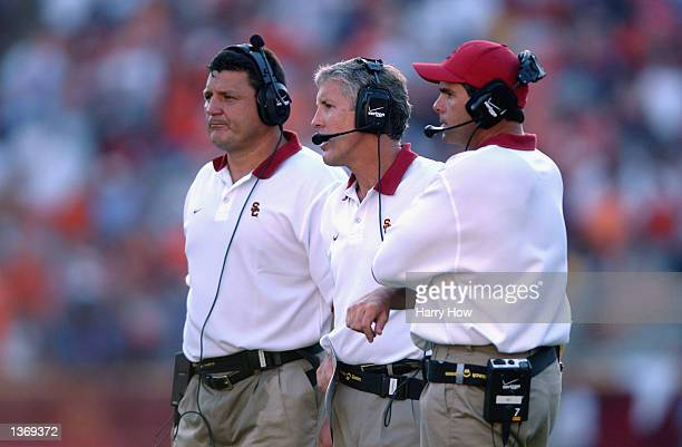 Head coach Pete Carroll of the USC Trojans , defensive line coach Ed Orgeron and linebackers coach Nick Holt look on from the sidelines during the...