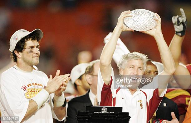 Head coach Pete Carroll of the USC Trojans holds up the championship trophy as quarterback Matt Leinart celebrates after defeating the Oklahoma...