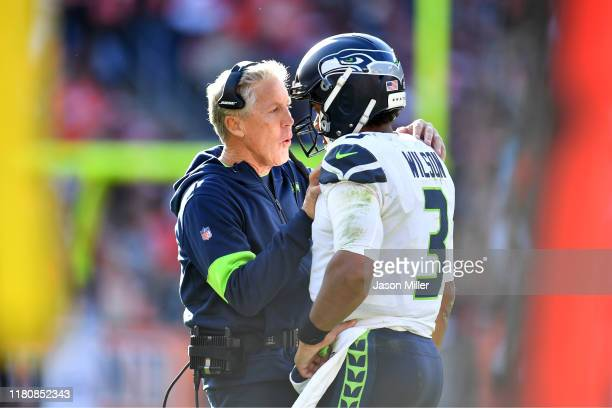 Head coach Pete Carroll talks with quarterback Russell Wilson of the Seattle Seahawks during the second half against the Cleveland Browns at...