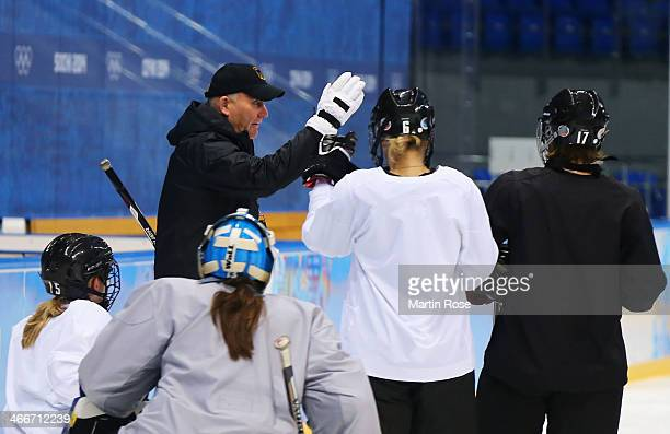Head coach Peter Kathan of the German women's ice hockey team speaks with his players dahead of the Sochi 2014 Winter Olympics at Shayba Arena on...