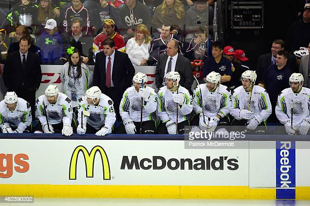 Head Coach Peter Laviolette and Assistant Coach Phil Housley of Team Toews look on from the bench area during the 2015 Honda NHL AllStar Game at...