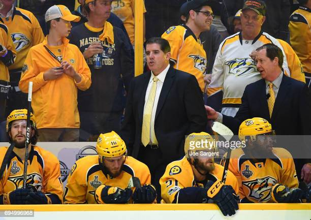 Head Coach Peter Laviolette of the Nashville Predators and assistant coach Phil Housley far right look on from the bench area in the second period of...