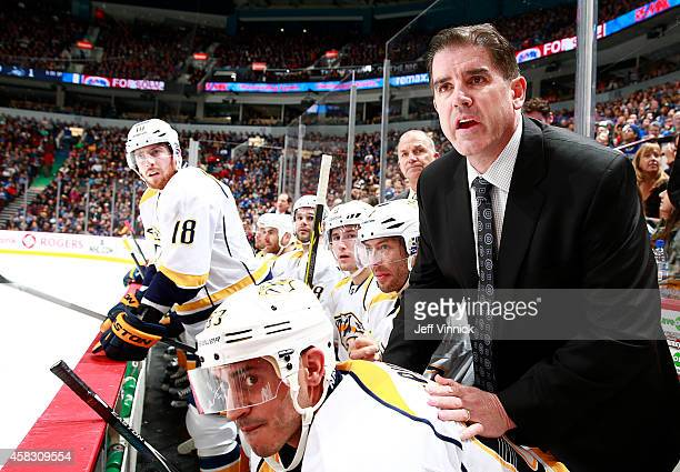 Head coach Peter Laviolette of the Nashville Predators leans on Mike Ribeiro of the Predators for a better view against the Vancouver Canucks during...