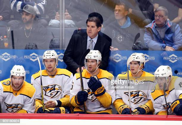 Head Coach Peter Laviolette of the Nashville Predators looks on from the bench during third period action against the Winnipeg Jets at the Bell MTS...