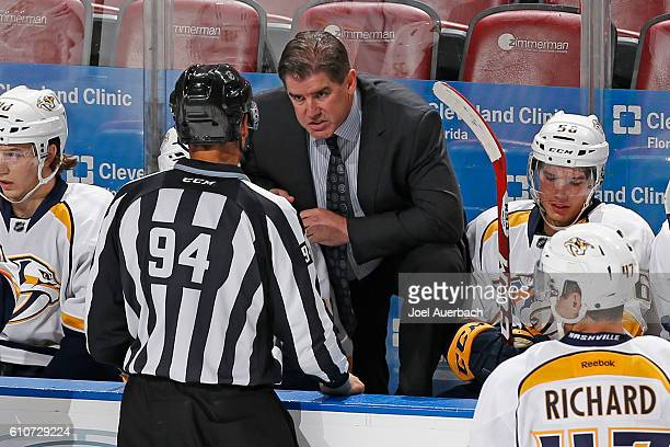 Head coach Peter Laviolette of the Nashville Predators talks to linesman Bryan Pancich during a break in action against the Florida Panthers during a...