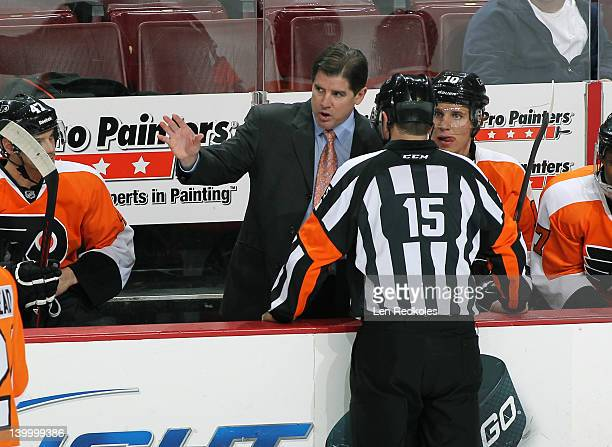 Head Coach Peter Laviolette of the Philadelphia Flyers discusses a call with Referee Stephane Auger during a stoppage in play against the Pittsburgh...