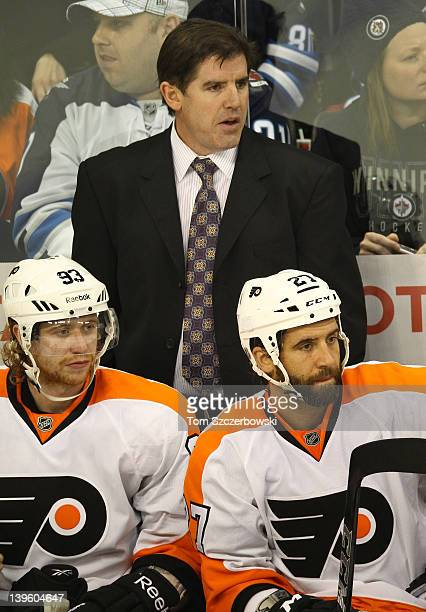 Head coach Peter Laviolette of the Philadelphia Flyers looks on from the bench with Jakub Voracek and Maxime Talbot during their NHL game against the...