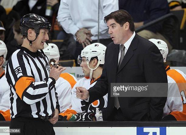 Head coach Peter Laviolette of the Philadelphia Flyers talks with referee Brad Watson before the start of the second period against the Boston Bruins...