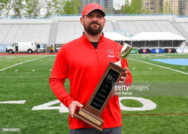 Head coach Peter Milliman of the Cornell Big Red poses for a photo with the Championship trophy following the game against the Yale Bulldogs in the...