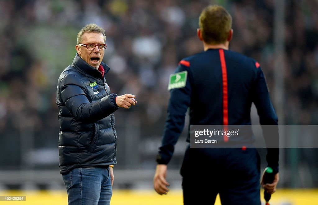Head coach Peter Stoeger discusses with assistant referee MArkus Haecker during the Bundesliga match between Borussia Moenchengladbach and 1. FC Koeln at Borussia Park Stadium on February 14, 2015 in Moenchengladbach, Germany.