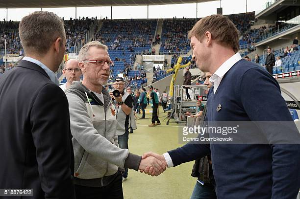 Head coach Peter Stoeger of 1 FC Koeln shakes hands with head coach Julian Nagelsmann of 1899 Hoffenheim prior to kickoff during the Bundesliga match...