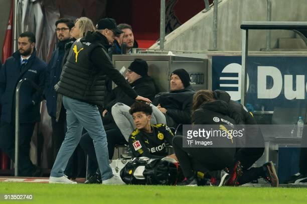 Head coach Peter Stoeger of Dortmund gestures and Jadon Sancho of Dortmund receives medical help during the Bundesliga match between 1 FC Koeln and...