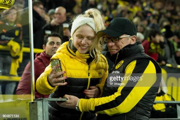 Head coach Peter Stoeger of Dortmund make a selfie with a fan prior the Bundesliga match between Borussia Dortmund and VfL Wolfsburg at Signal Iduna...
