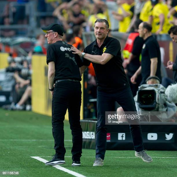 Head coach Peter Stoeger of Dortmund shakes hands with Michael Zorc of Dortmund during the Bundesliga match between Borussia Dortmund and Bayer 04...